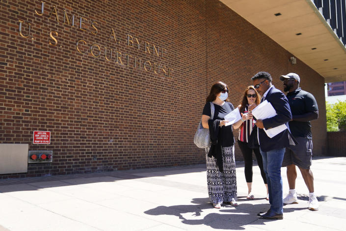 """Former NFL players Clarence Vaughn III, right, Ken Jenkins, second right, along with their wives, Brooke Vaughn, third right, and Amy Lewis, carrie tens of thousands of petitions demanding equal treatment for everyone involved in the settlement of concussion claims against the NFL, to the federal courthouse in Philadelphia, Friday, May 14, 2021. Thousands of retired Black professional football players, their families and supporters are demanding an end to the controversial use of """"race-norming"""" to determine which players are eligible for payouts in the NFL's $1 billion settlement of brain injury claims, a system experts say is discriminatory. (AP Photo/Matt Rourke)"""