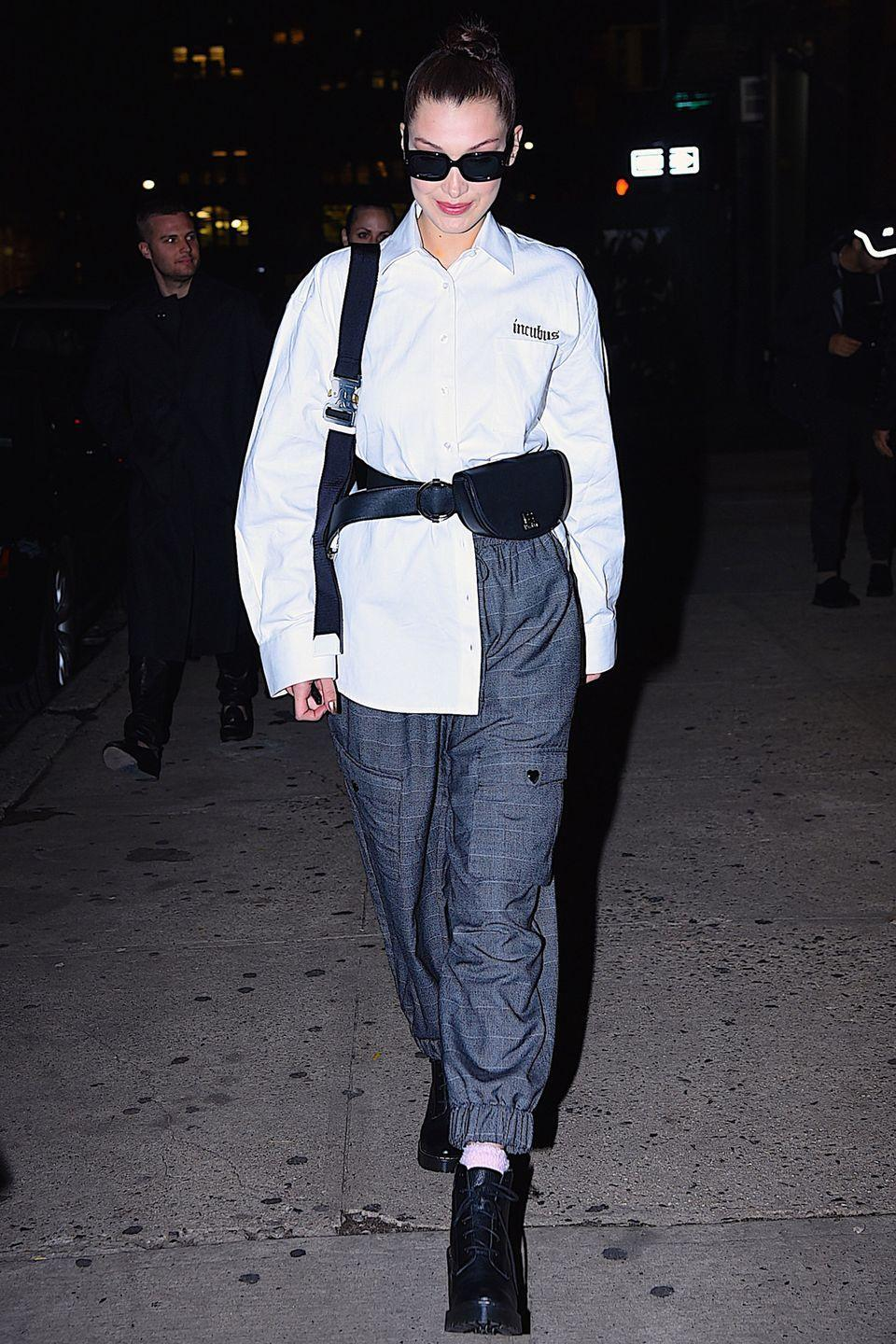 <p>In a white button-down shirt, fanny pack, cinched plaid pants, lace-up heeled boots, and rectangular sunglasses while out in New York.</p>