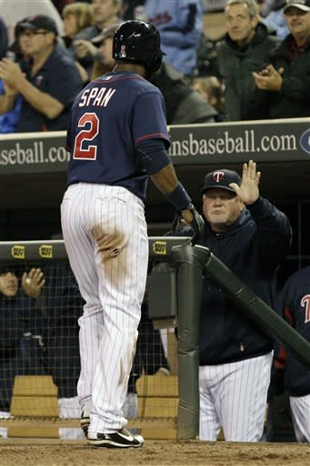 Minnesota Twins manager Ron Gardenhire, right, congratulates Denard Span after he scored on a Josh Willingham double in the fifth inning of a baseball game against the Toronto Blue Jays Friday, May 11, 2012, in Minneapolis. (AP Photo/Jim Mone)