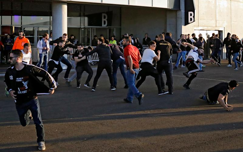 Fans also fight outside the stadium - Credit: AP