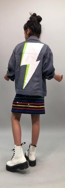 """<p>""""Claudia's got this great jean jacket that she wears . . . it kind of fits her like a '90s vibe because it's oversize for her. We painted this lightning bolt on the back, but you never see it because on camera, we never see the back of it.""""</p>"""