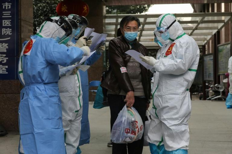 Medical staff check information as patients infected by the coronavirus transfer between hospitals in Wuhan
