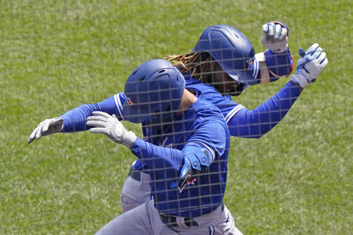 Toronto Blue Jays first baseman Vladimir Guerrero Jr., right, celebrates with a teammate after hitting a solo home run during the second inning of a baseball game against the New York Yankees, Sunday, April 4, 2021, at Yankee Stadium in New York. (AP Photo/Kathy Willens)