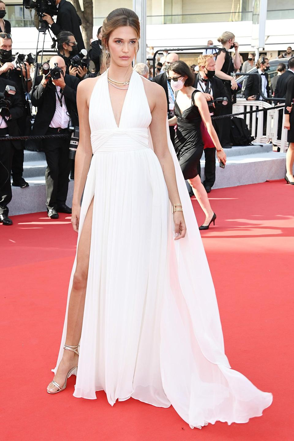 """Model Noelle Capri channeled the early 2000s in a white halter dress with a high slit and dramatic cape. <span class=""""copyright"""">Photo: Daniele Venturelli/WireImage.</span>"""