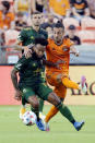 Portland Timbers midfielder Eryk Williamson, left, is pulled back by Houston Dynamo forward Maximiliano Urruti, right, as they chase the ball during the first half of an MLS soccer match Wednesday, June 23, 2021, in Houston. (AP Photo/Michael Wyke)