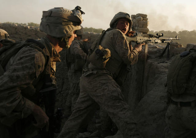 <p>U.S. marines fire during a Taliban ambush as they carry out an operation to clear an area in Helmand province, Oct. 9, 2009. (Photo: Asmaa Waguih/Reuters) </p>