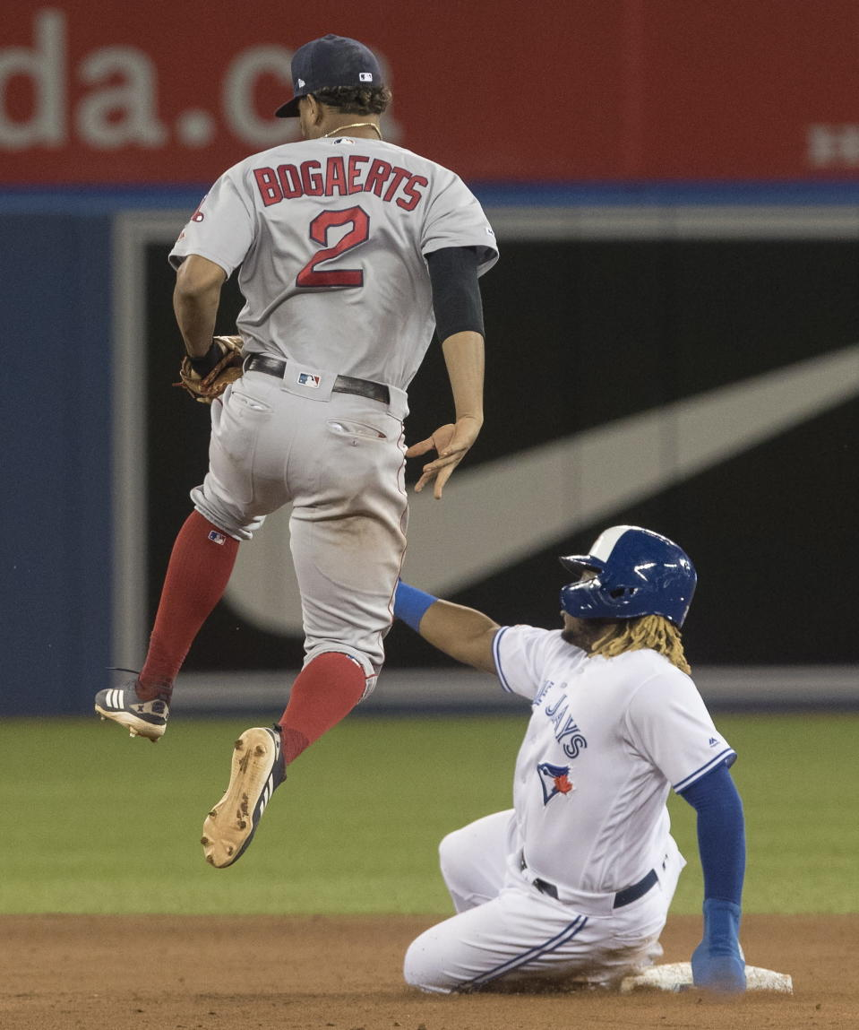Toronto Blue Jays' Vladimir Guerrero Jr. is forced out at second base as Boston Red Sox shortstop Xander Bogaerts (2) leaps out of the way during the fifth inning of a baseball game Thursday, Sept. 12, 2019, in Toronto. (Fred Thornhill/The Canadian Press via AP)