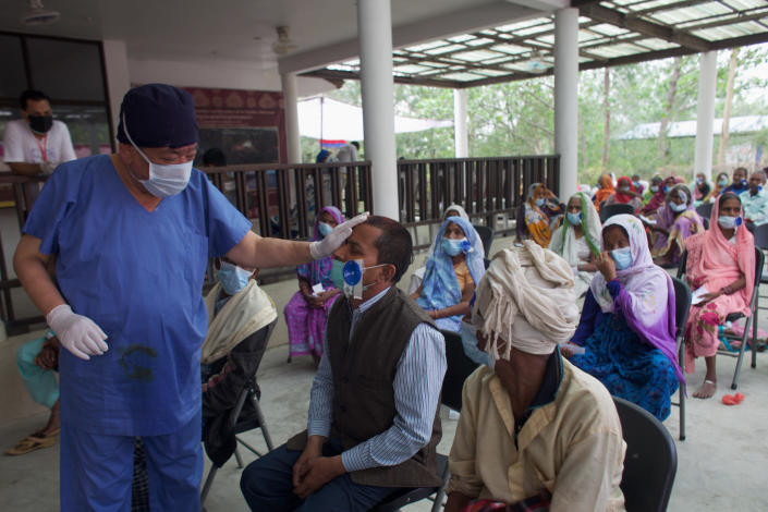 """Nepal's """"God of Sight"""", Dr. Sanduk Ruit checks a patient's eye sight after his eye patches are removed at an eye camp in Lumbini, 288 kilometers (180 miles) south west of Kathmandu, Nepal, March 31, 2021. The eye doctor renowned for his innovative and inexpensive cataract surgery for the poor is taking his work beyond the Himalayan mountains to other parts of the world so there is no more unnecessary blindness in the world. Ruit, who has won many awards for his work and performed some 130,000 cataract surgery in the past three decades, is aiming to expand his work beyond the borders of his home country and the region to go globally. (AP Photo/Bikram Rai)"""