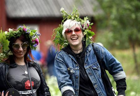 FILE PHOTO: Girls wearing flower garlands celebrate the summer solstice during the Seurasaari open-air museum's Midsummer Eve festival in Helsinki