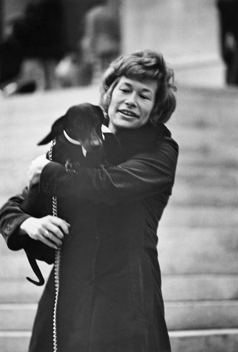 Iris Love, American archaeologist, smiling with short curly hair, wearing a brown suede coat and holding her dachshund. (Photo byJack Robinson/Condé Nast via Getty Images)