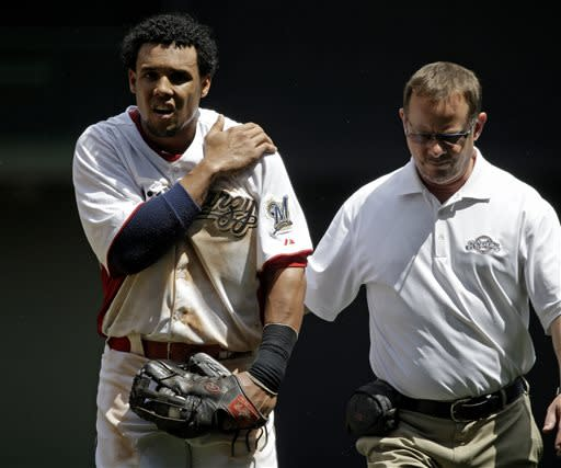 Milwaukee Brewers center fielder Carlos Gomez, left, is helped off the field after he hit the wall while catching a ball hit by Atlanta Braves' Andrelton Simmons during the fourth inning of a baseball game on Sunday, June 23, 2013, in Milwaukee. Gomez left the game. (AP Photo/Morry Gash)