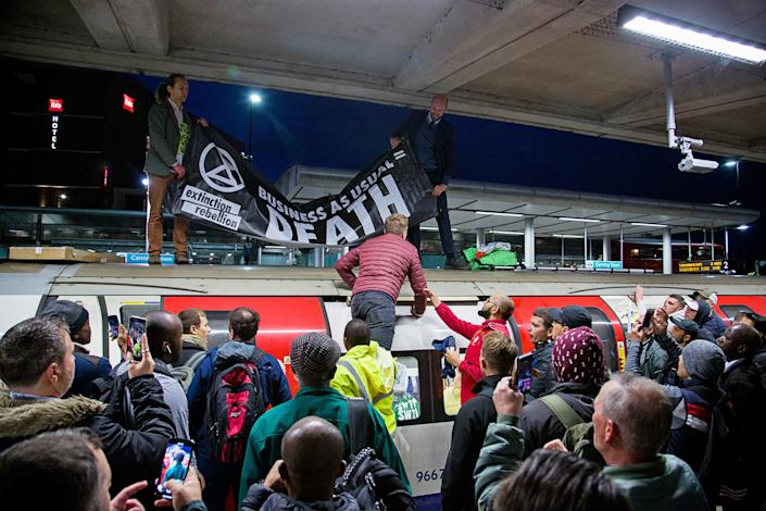 XR activists climb onto a train at London's Canning Town station, prompting a standoff with commuters, on Oct. 17. | Extinction Rebellion