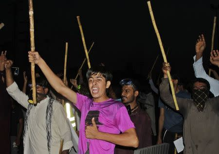Supporters of Muhammad Tahirul Qadri, Sufi cleric and leader of political party PAT, chant slogans as they wave sticks during a protest in Lahore