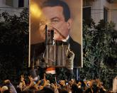 FILE - In this Jan. 25, 2011 file photo, demonstrators deface a poster of Egyptian President Hosni Mubarak in Alexandria, Egypt. The 2011 uprising led to the quick ouster of autocrat Mubarak. A decade later, thousands are estimated to have fled abroad to escape a state, headed by President Abdel Fattah el-Sissi, that is even more oppressive. (AP Photo, File)