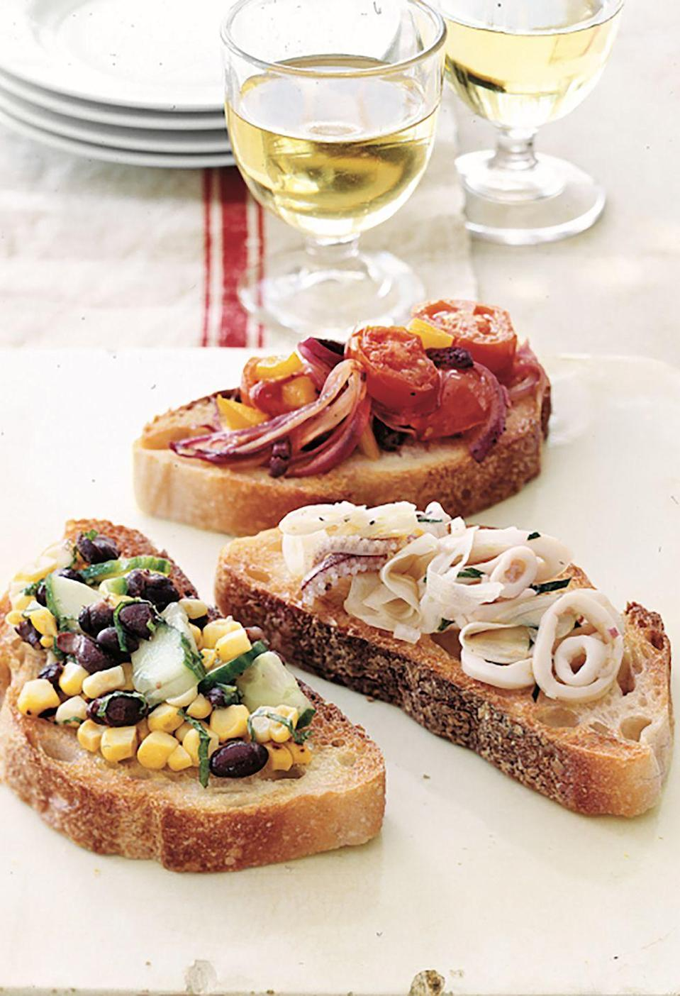 """<p>A single baguette, sliced and used as a foundation, yields a host of easy-to-assemble appetizers. Prepare toppings the day before and add them just before serving. Offer guests small plates and forks to scoop up the extras.</p><p><strong><a href=""""https://www.countryliving.com/food-drinks/recipes/a1024/bruschetta-3140/"""" rel=""""nofollow noopener"""" target=""""_blank"""" data-ylk=""""slk:Get the recipe"""" class=""""link rapid-noclick-resp"""">Get the recipe</a>.</strong></p>"""
