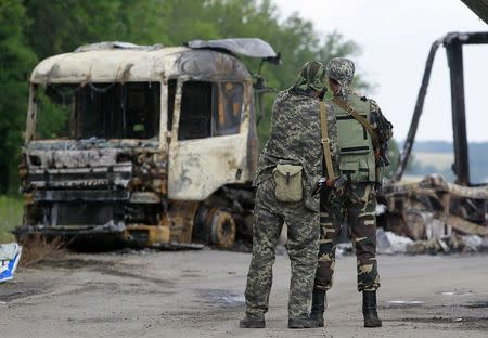 Pro-Russian separatists stand guard at a checkpoint near a burnt truck outside Luhansk
