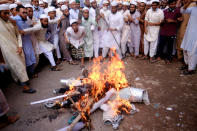 """Supporters of Islami Oikya Jote, an Islamist political party, burn an effigy representing French President Emmanuel Macron during a protest against the publishing of caricatures of the Prophet Muhammad they deem blasphemous, in Dhaka, Bangladesh, Wednesday, Oct. 28, 2020. Muslims in the Middle East and beyond on Monday called for boycotts of French products and for protests over the caricatures, but Macron has vowed his country will not back down from its secular ideals and defense of free speech. Posters read """"France is the enemy of humanity. World citizens fight back."""" second left, """"Muslims of the world stand against insults to the prophet,"""" third right and """"Stop buying products from France. In the name of the Prophet,"""" left. (AP Photo/Mahmud Hossain Opu)"""