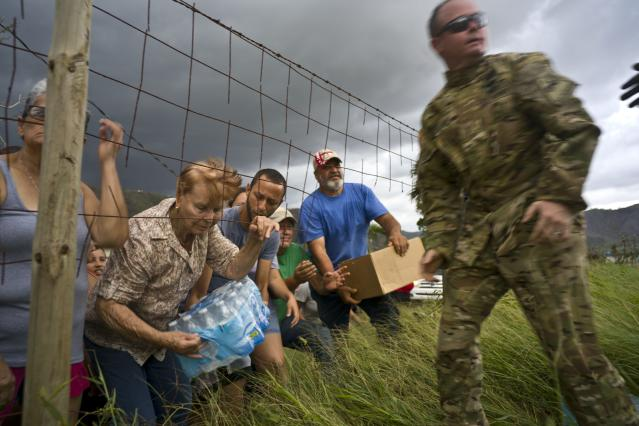 <p>A member of the Puerto Rican National Guard delivers food and water brought via helicopter to victims of Hurricane Maria, to the San Lorenzo neighborhood of Morovis, Puerto Rico, Saturday, Oct. 7, 2017. (Photo: Ramon Espinosa/AP) </p>