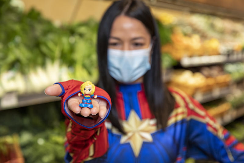 A woman dressed as Captain Marvel, holding a Captain Marvel Ooshie, which Woolworths shoppers will be able to collect across Australia