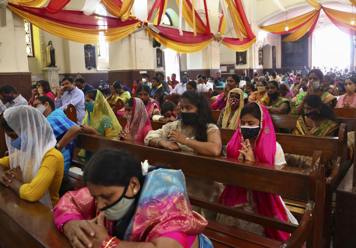 Indian Christians wearing face masks as a precaution against the coronavirus attend a Christmas mass at St. Joseph Cathedral in Hyderabad, India, Friday, Dec. 25, 2020. (AP Photo/Mahesh Kumar A.)