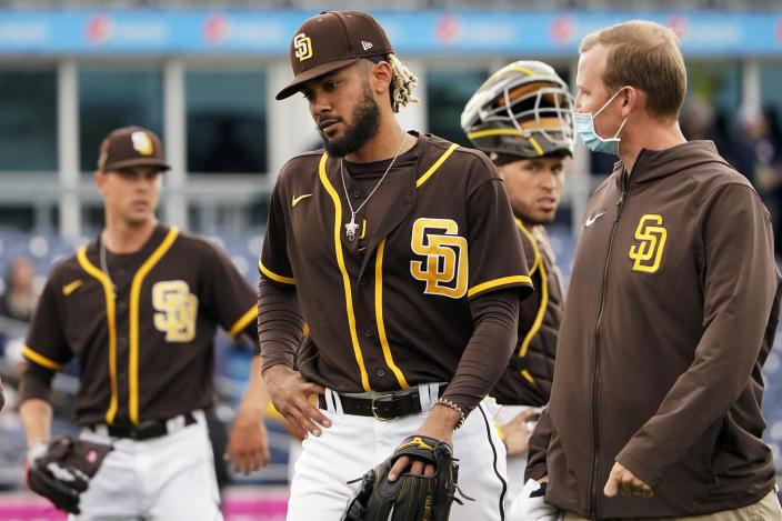 San Diego Padres shortstop Fernando Tatis Jr., center, leaves the field following an injury in the third inning of a spring training baseball game against the Cincinnati Reds Tuesday, March 23, 2021, in Peoria, Ariz. (AP Photo/Sue Ogrocki)