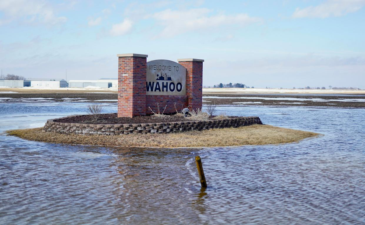 A Welcome to Wahoo sign stands in flood waters outside Wahoo, Neb., Wednesday, March 13, 2019. Record flooding swamped the central U.S. this week.