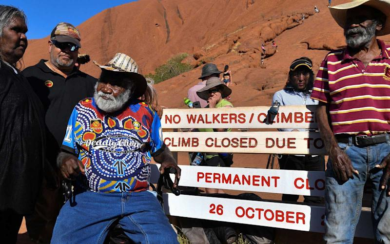 Aboriginal elders stand beside new signage at the base of Uluru, also known as Ayers Rock, ahead of the day's end marking the start of a permanent ban on climbing the monolith, at Uluru-Kata Tjuta National Park in Australia's Northern Territory on October 25, 2019. | SAEED KHAN/Getty Images