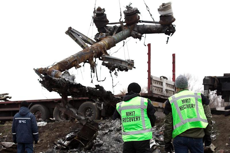 Members of the Dutch expert team watch as parts of the wreckage of the Malaysia Airlines Flight MH17 are removed and loaded on a truck at the crash site near Grabove in eastern Ukraine, on November 16, 2014 (AFP Photo/Menahem Kahana)