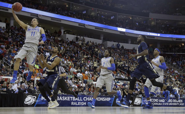 Memphis guard Michael Dixon Jr. (11) shoots against George Washington guard Miguel Cartagena (3) during the second half of an NCAA college basketball second-round tournament game, Friday, March 21, 2014, in Raleigh. (AP Photo/Gerry Broome)