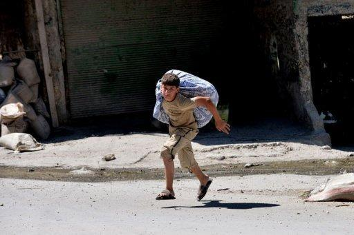 """A Syrian youth runs to escape the Al Mashad neighbourhood during clashes between rebel fighters and government forces in the northern city of Aleppo on August 25. Syrian President Bashar al-Assad said on Sunday the foreign """"conspiracy"""" against his country would be defeated, as his forces were accused of a bloody rampage"""