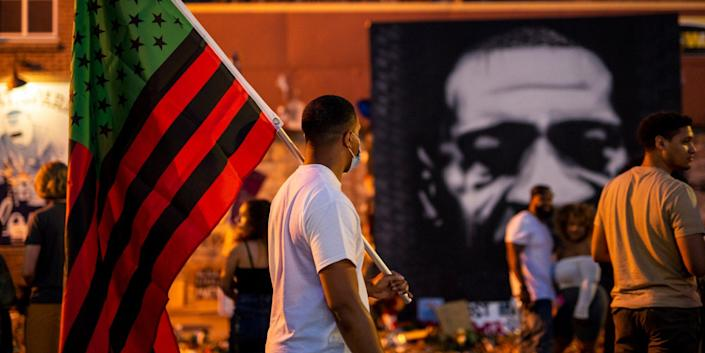 A man carries a Black Liberation flag through a Juneteenth celebration at the memorial for George Floyd outside Cup Foods in Minneapolis, Minnesota, on June 19, 2020.