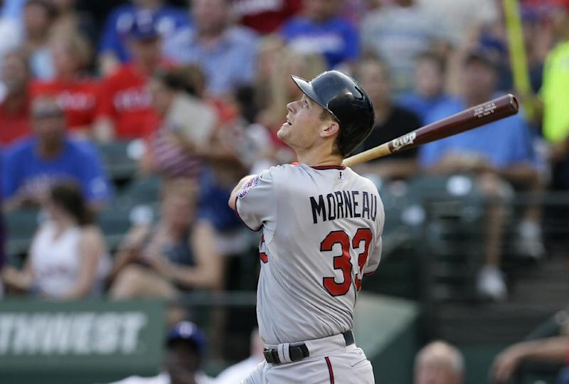 In this photo taken Friday, Aug. 30, 2013, file photo Minnesota Twins' Justin Morneau (33) follows through on a fly out to center in the first inning of a baseball game against the Texas Rangers in Arlington, Texas. The Twins have traded Morneau to the Pittsburgh Pirates on Saturday, Aug. 31, 2013,, sending the veteran first baseman to a playoff-contending team for the final month of the season. (AP Photo/Tony Gutierrez, File)