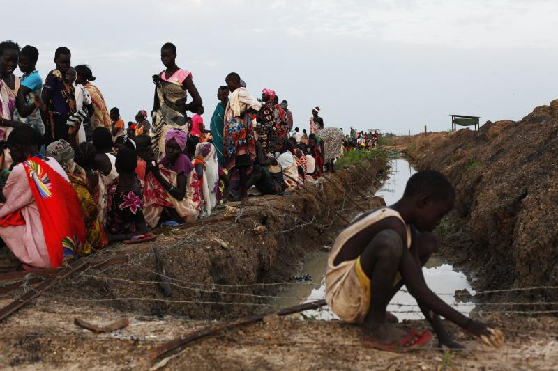 vA displaced child tries to get mud off his hands as displaced women wait for food distribution to start in the IDP camp in the UN base in Bentiu