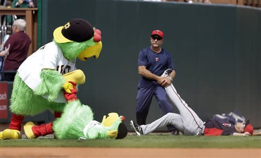 The Pittsburgh Pirates parrot mascot stretches out Lil Parrot's legs imitating Minnesota Twins center fielder Darin Mastroianni as he is stretched before an exhibition spring training baseball game, Saturday, March 9, 2013, in Bradenton, Fla. (AP Photo/Carlos Osorio)