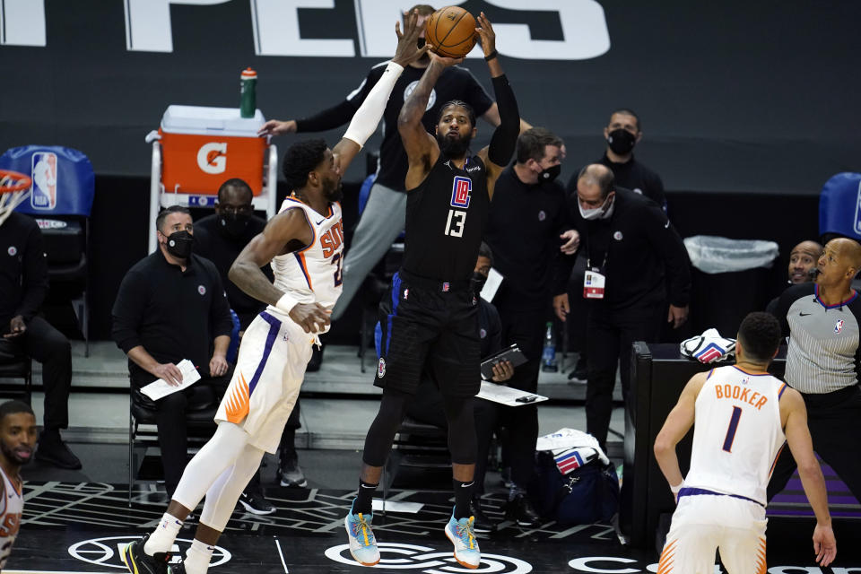 Los Angeles Clippers guard Paul George (13) makes a 3-point basket over Phoenix Suns center Deandre Ayton during the second half of an NBA basketball game Thursday, April 8, 2021, in Los Angeles. (AP Photo/Marcio Jose Sanchez)