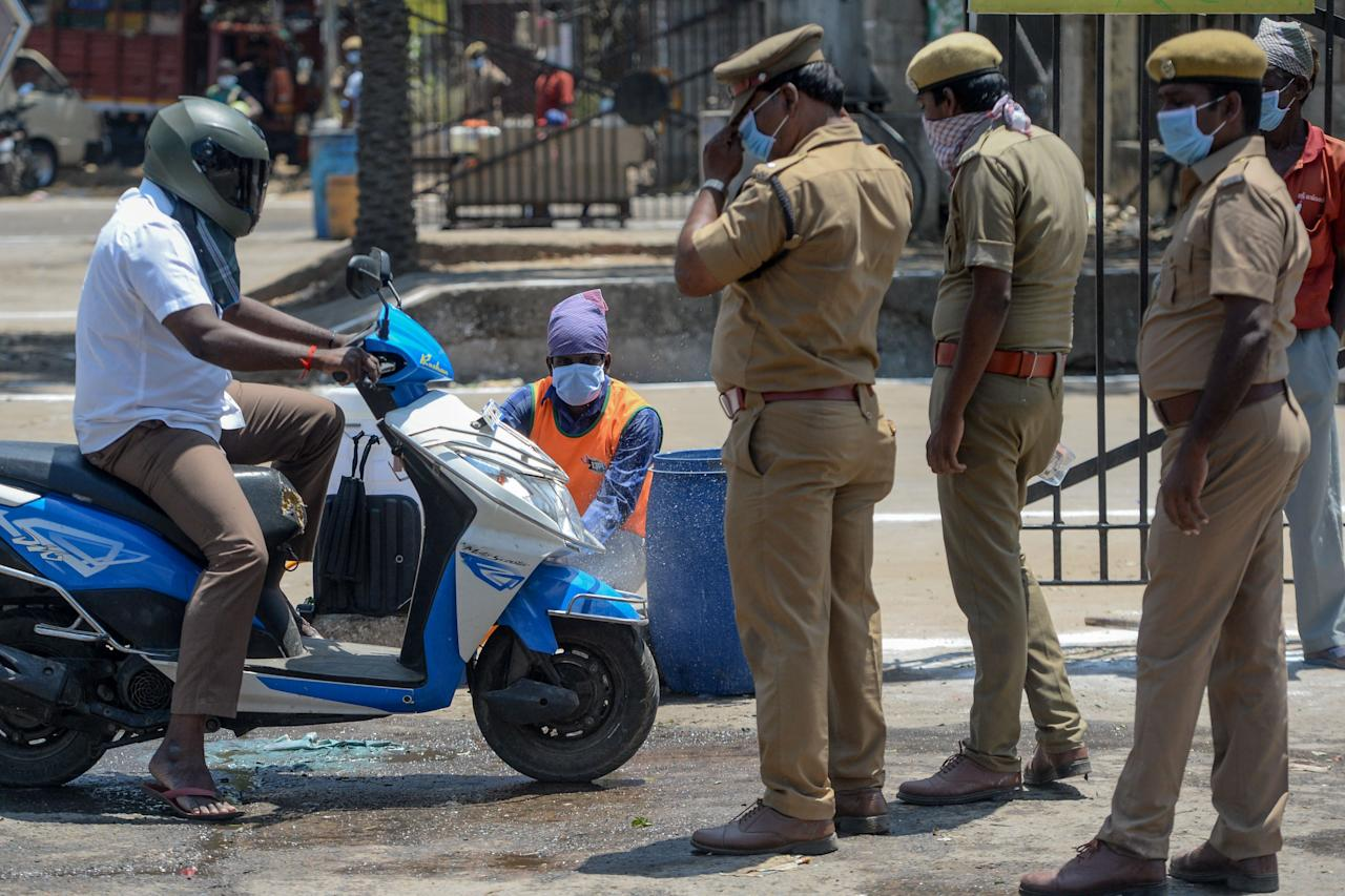 Policemen stand beside as a health worker (C) sprays disinfectant on a scooter coming out of a market during a government-imposed nationwide lockdown as a preventive measure against the COVID-19 coronavirus, in Chennai on March 27, 2020. (Photo by Arun SANKAR / AFP) (Photo by ARUN SANKAR/AFP via Getty Images)
