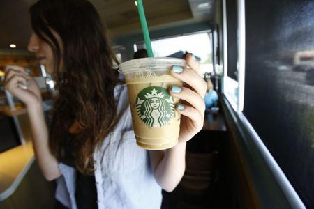 A patron holds an iced beverage at a Starbucks coffee store in Pasadena