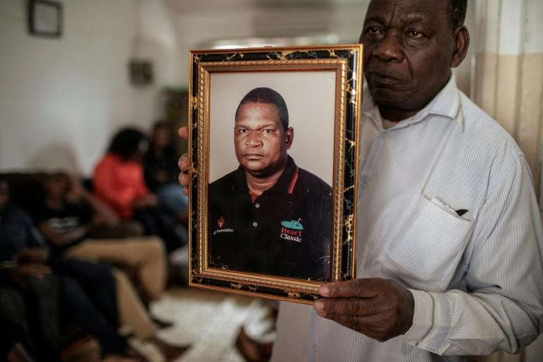 Anastacio Matavele, seen here in a portrait held by a family representative, was killed in the run-up to Mozambique's October election (AFP Photo/GIANLUIGI GUERCIA)
