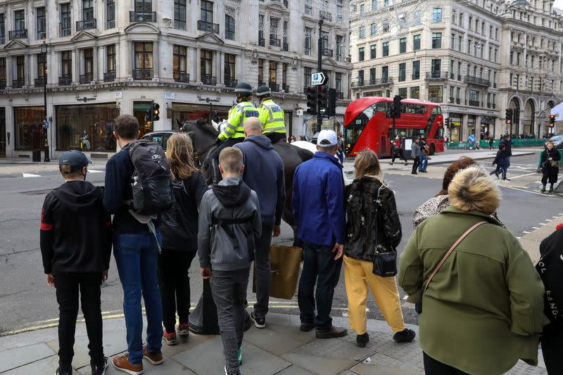 People wait to cross Regent Street in London