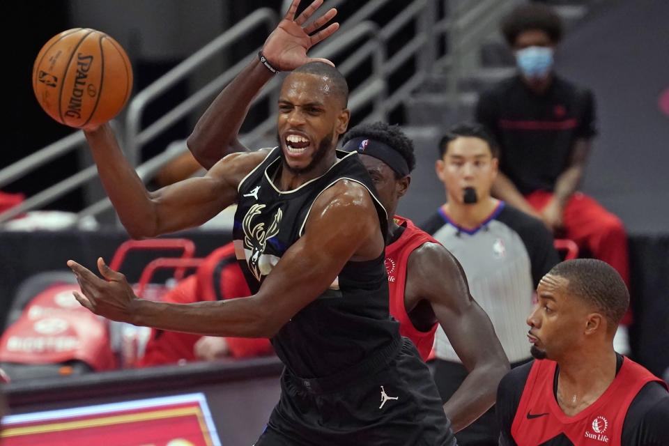 Milwaukee Bucks forward Khris Middleton (22) passes the ball in front of Toronto Raptors forward Pascal Siakam (43) and guard Norman Powell (24) during the first half of an NBA basketball game Wednesday, Jan. 27, 2021, in Tampa, Fla. (AP Photo/Chris O'Meara)