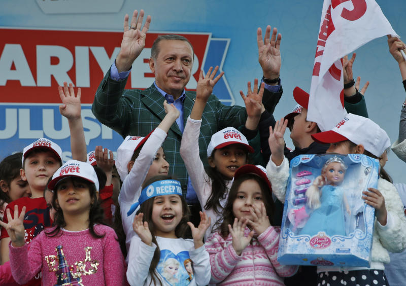 FILE - In this Saturday, April 15, 2017 photo, Turkey's President Recep Tayyip Erdogan waves to supporters as he poses with children during the last rally ahead of Sunday's referendum, in Istanbul. Few men can claim to have dominated politics in Turkey - or polarized his people - as much as Erdogan, the 63-year-old president who has urged his nation to approve reforms that will greatly expand his powers. (AP Photo/Lefteris Pitarakis, file)