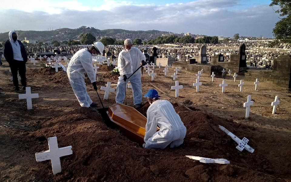 Funeral workers carry out burials of Covid-19 victims at Inhauma Cemetery, north of the city, in Rio de Janeiro, Brazil - Fabio Teixeira/Anadolu Agency