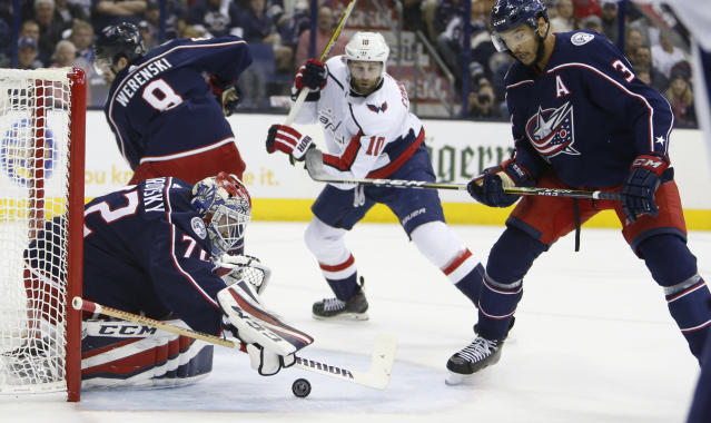 Columbus Blue Jackets' Sergei Bobrovsky, left, of Russia, covers the puck as teammate Seth Jones, right, and Washington Capitals' Brett Connolly look for the rebound during the first period of Game 6 of an NHL first-round hockey playoff series Monday, April 23, 2018, in Columbus, Ohio. (AP Photo/Jay LaPrete)