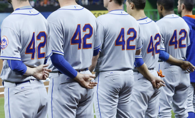 New York Mets players, all wearing No. 42, stand during the singing of the national anthem before a baseball game against the Miami Marlins, Saturday, April 15, 2017, in Miami. Every Major League player wore No. 42 on Saturday to honor Jackie Robinson. (AP Photo/Wilfredo Lee)