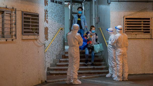PHOTO: Residents leave the Hong Mei House residential building at Cheung Hong Estate as officials wearing protective gear stand guard outside the entrance, in Hong Kong's Tsing Yi area, China, on Feb. 11, 2020. (Billy H.c. Kwok/Getty Images)