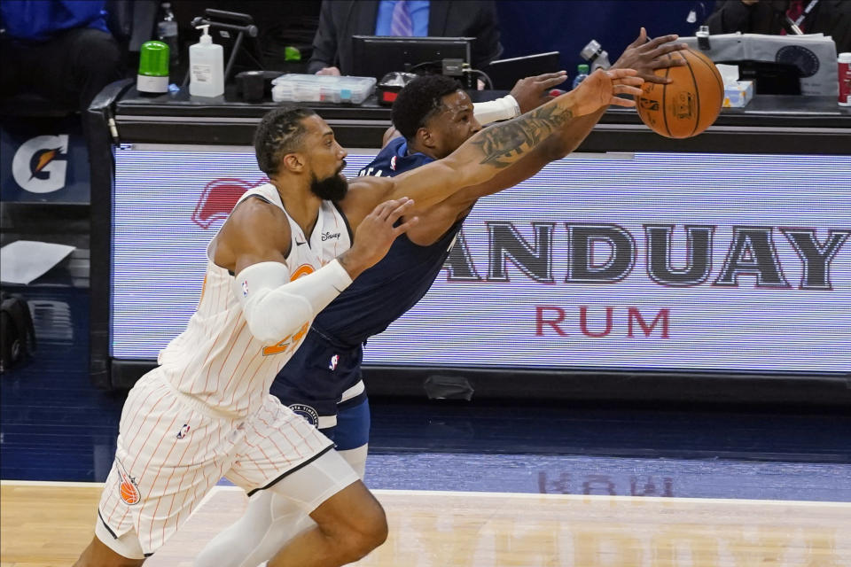 Orlando Magic's Khem Birch, left, and Minnesota Timberwolves' Malik Beasley chase the ball during the first half of an NBA basketball game Wednesday, Jan. 20, 2021, in Minneapolis. (AP Photo/Jim Mone)