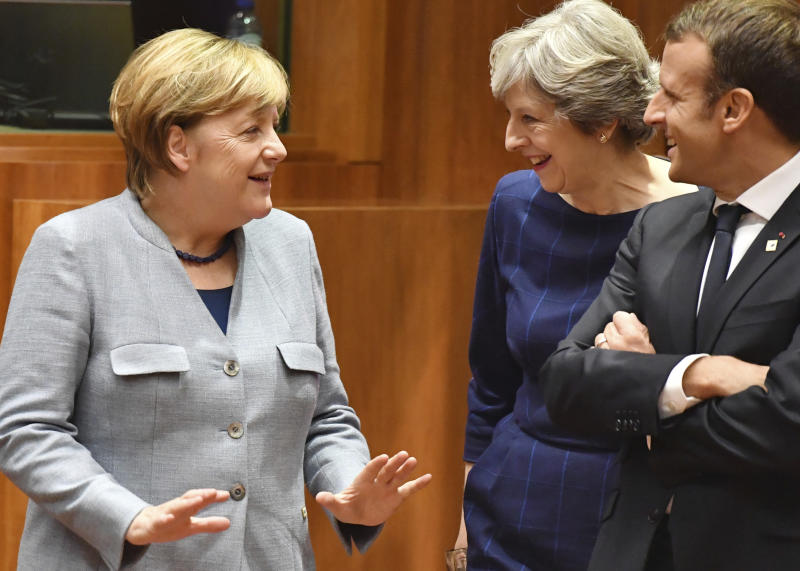 British Prime Minister Theresa May, center, speaks with French President Emmanuel Macron, right, and German Chancellor Angela Merkel, left, during a round table meeting at an EU summit in Brussels on Thursday, Oct. 19, 2017. British Prime Minister Theresa May headed to a European Union summit Thursday with a pledge to treat EU residents well once Britain leaves the bloc. (AP Photo/Geert Vanden Wijngaert)