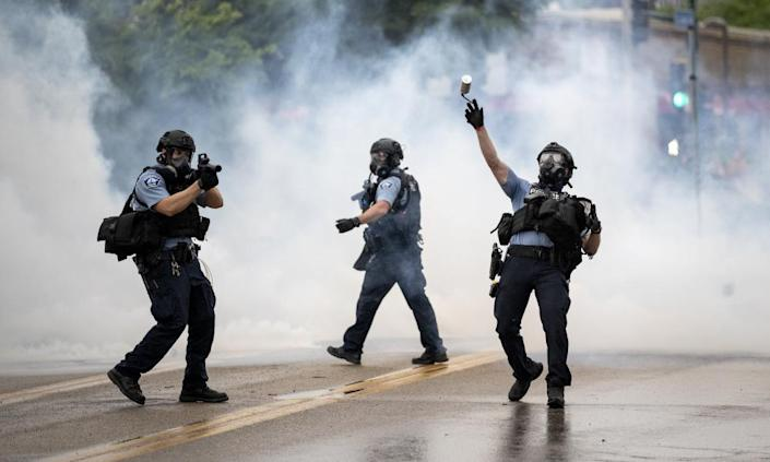 "<span class=""element-image__caption"">A police officer throws a tear gas canister towards protesters.</span> <span class=""element-image__credit"">Photograph: Carlos Gonzalez/AP</span>"