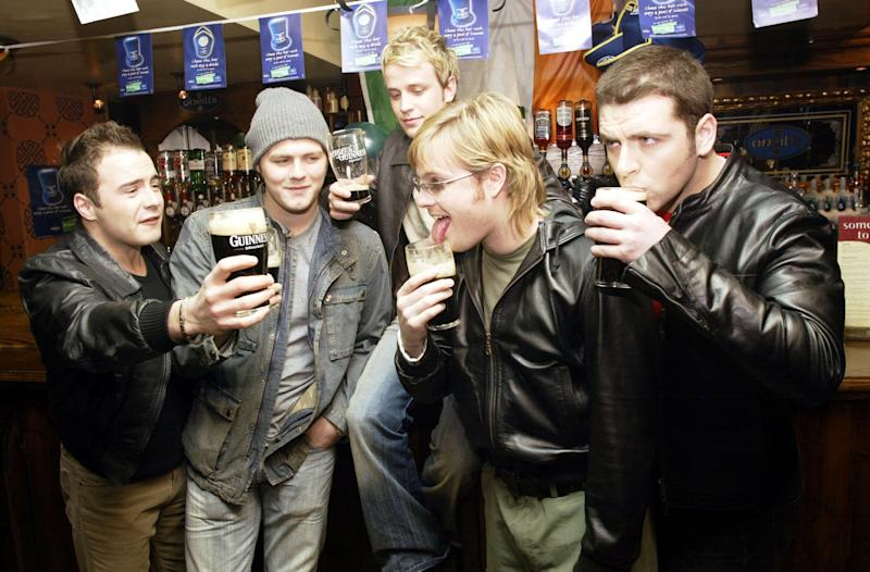 "LONDON - MARCH 16: (L to R) Shane Filan, Brian McFadden, Kian Egan, Nicky Byrne, and Mark Feehily, from the Irish boy band ""Westlife"", enjoy a pint of Guinness at O'Neills in London on March 16, 2003. The band were celebrating St. Patrick's Day twenty-four hours in advance by taking over the pub for the afternoon. St. Patrick's Day is officially March 17. (Photo by Dave Hogan/Getty Images)"