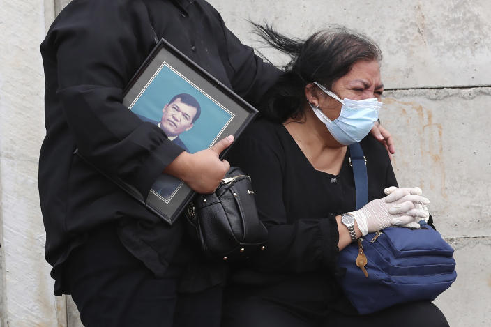 Family members react during the burial of relative at the special section of Jombang cemetery opened to accommodate the surge in deaths during coronavirus outbreak in Tangerang, Indonesia, Tuesday, Jan. 26, 2021. Indonesia has reported more cases of the virus than any other countries in Southeast Asia. (AP Photo/Tatan Syuflana)